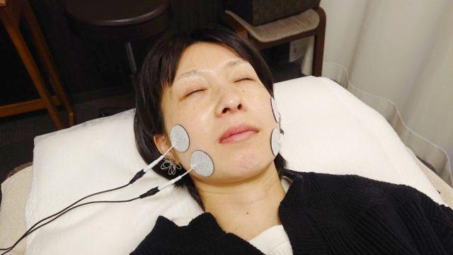 EMSという心地よい機械の電気刺激で筋肉を刺激し、表情筋をリフトアップさせている画像。